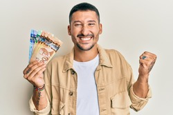 Handsome man with tattoos holding canadian dollars screaming proud, celebrating victory and success very excited with raised arm