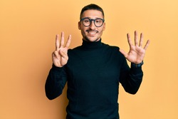 Handsome man with tattoos wearing turtleneck sweater and glasses showing and pointing up with fingers number eight while smiling confident and happy.