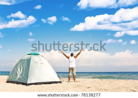 handsome man with tent enjoying camping recreation at a wonderful tranquil beach