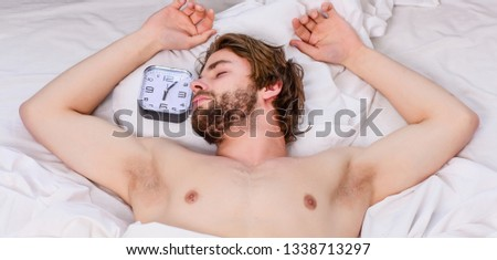 Handsome man yawning and stretching his arms up.Picture showing young man stretching in bed. Man feeling tired and does not want to get up