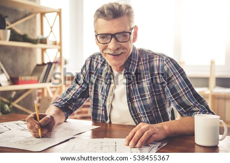 Handsome mature architect in casual clothes and glasses is looking at camera and smiling while working with drafts in office