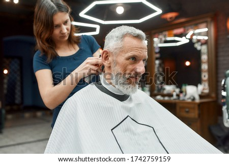 Handsome mature bearded man sitting in barbershop chair while female barber working with hair clipper, making haircut. Barbershop. Beauty salon. Barber tools. Mens haircut