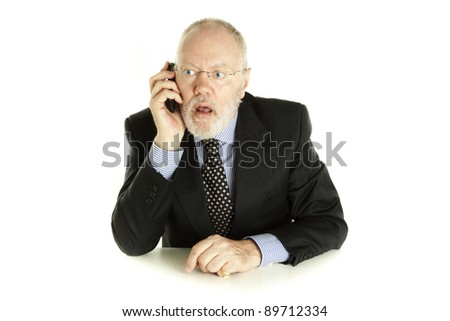 Handsome mature business man is having surprising phone call on white background