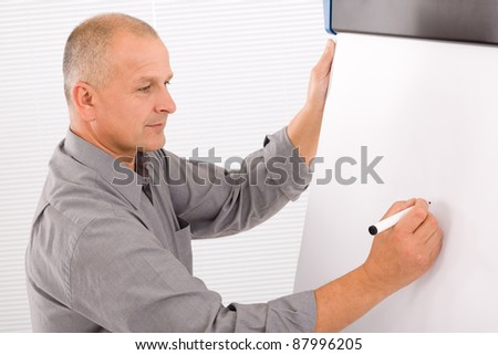Handsome mature businessman writing at empty flip chart looking aside