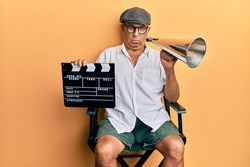 Handsome mature director man holding video film clapboard and louder skeptic and nervous, frowning upset because of problem. negative person.