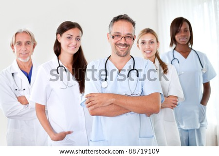 Handsome mature doctor smiling at the camera with folded hands and colleagues in background - stock photo