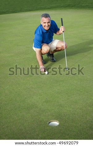 handsome mature male golfer in his 40s-50s on the putting green ready to make a putt