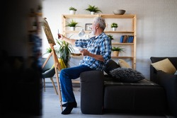 Handsome mature man artist paints on canvas painting on the easel