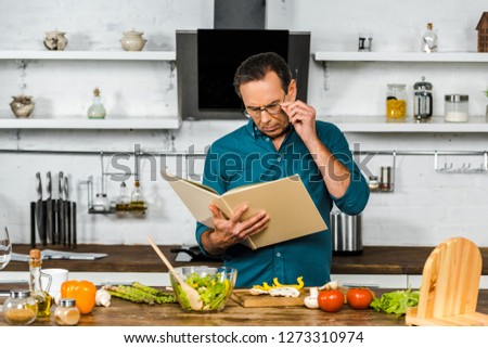 handsome mature man cooking in kitchen and looking at cookbook