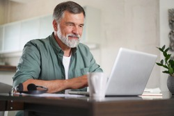 Handsome mature man in casual suit sitting at the table in home office and working at laptop
