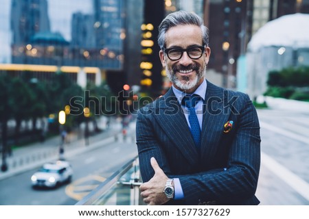 Handsome mature man in glasses and business suit with arms crossed smiling and standing on background of evening New York street while looking at camera