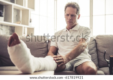 Handsome mature man is touching his broken leg in gypsum while sitting on sofa at home #617819921
