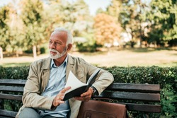 Handsome mature man reading book outdoors.