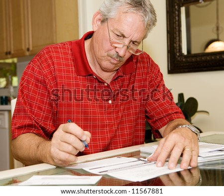 Handsome mature man signing papers beside a stack of bills.