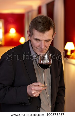 Handsome mature man swirling red wine in a glass and sniffing the bouquet during wine tasting in romantic red interior