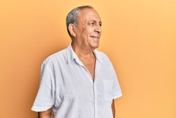 Handsome mature man wearing casual white shirt looking away to side with smile on face, natural expression. laughing confident.