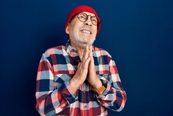 Handsome mature man wearing hipster look with wool cap begging and praying with hands together with hope expression on face very emotional and worried. begging.