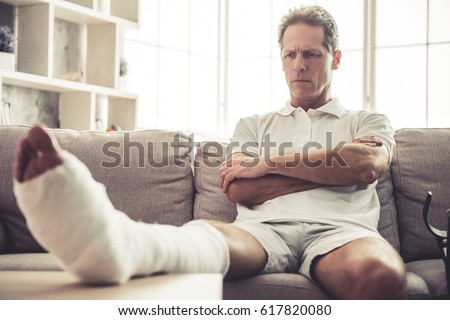 Handsome mature man with broken leg in gypsum is sitting seriously with crossed arms on sofa at home