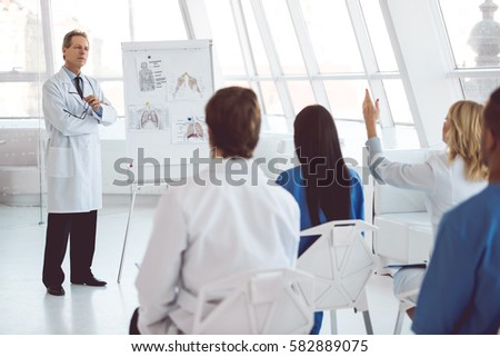 Handsome mature medical doctor is giving lecture for his colleagues using a whiteboard and schemes