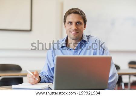 Handsome mature student learning and sitting in classroom while smiling at camera
