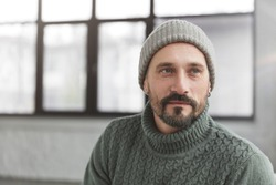Handsome mature stylish man with beard and mustache dressed in warm knitted clothes, looks thoughtfully aside as thinks about creative project. Fashionable middle aged attractive male indoor