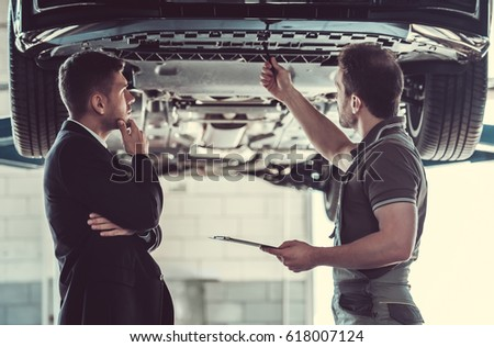 Handsome mechanic and businessman are examining car and discussing repair in auto service