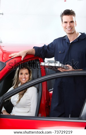Handsome mechanic and woman in auto repair shop.