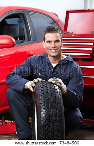 Handsome mechanic changing  wheels in auto shop.