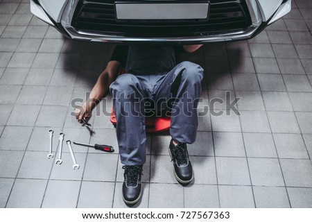 Handsome mechanic in uniform is working in auto service with wrenches. Man on portable plastic repair creeper. Car repair and maintenance.