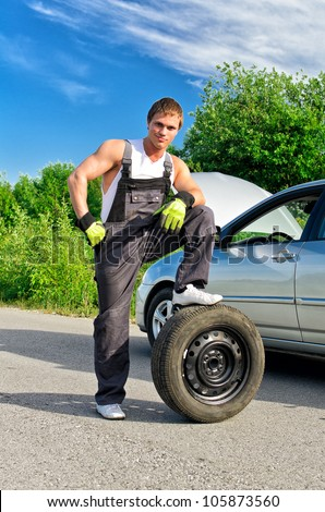 Handsome mechanic standing on a tire on the road - stock photo