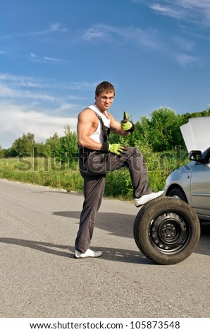 Handsome mechanic with a tire on a road