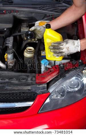Handsome mechanic working in auto repair shop.