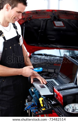 Handsome mechanic working in auto repair shop.