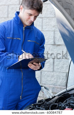 Handsome mechanic writing on a clipboard standing in front of a car at work