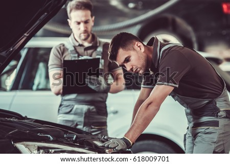 Handsome mechanics in uniform are examining car while working in auto service Foto stock ©