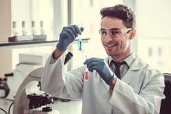 Handsome medical doctor in gloves and glasses is smiling while working with test tubes at the lab