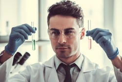 Handsome medical doctor in gloves and glasses is working with test tubes at the lab