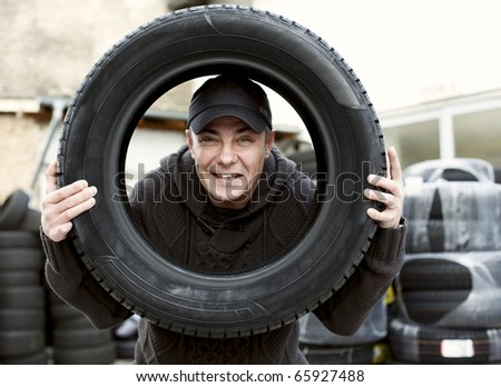 handsome Men with friendly face and Car Tire at an auto shop