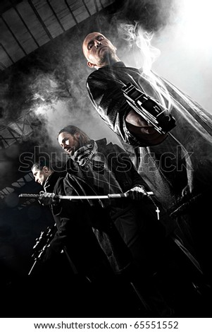 Handsome men with weapons - stock photo