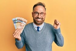 Handsome middle age business man holding canadian dollars screaming proud, celebrating victory and success very excited with raised arm