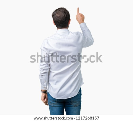 Handsome middle age elegant senior business man wearing glasses over isolated background Posing backwards pointing behind with finger hand