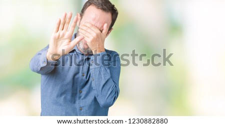 Handsome middle age elegant senior man over isolated background covering eyes with hands and doing stop gesture with sad and fear expression. Embarrassed and negative concept.