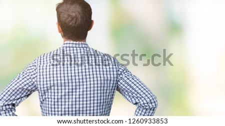 Handsome middle age elegant senior man wearing glasses over isolated background standing backwards looking away with arms on body