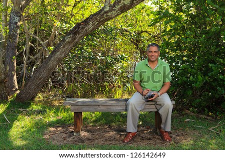 Handsome middle age hispanic man in a park setting.