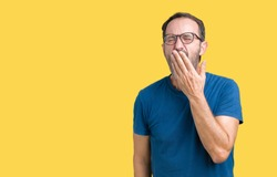 Handsome middle age hoary senior man wearin glasses over isolated background bored yawning tired covering mouth with hand. Restless and sleepiness.
