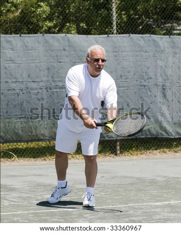 handsome middle age male tennis player hitting forehand stroke on tennis court at club