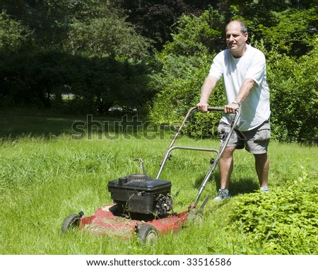 handsome middle age man cutting overgrown grass with old fashioned lawn mower at suburban house