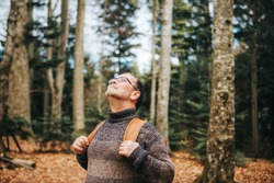 Handsome middle age man hiking in forest, wearing pullover, backpack and glasses
