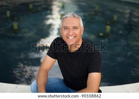 Handsome middle age man in an outdoor urban setting by a fountain.
