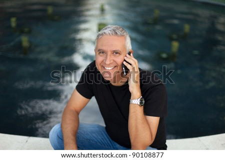 Handsome middle age man in an outdoor urban setting with a wireless phone by a fountain.